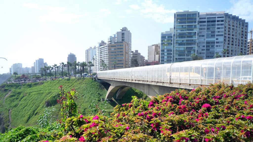 Skyscrapers and skyline overlooking coast and flower garden next to bridge in Miraflores Lima Peru - how to Miraflores