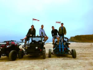 Four of us ATV riding quad bikes on beach in the Paracas National Reserve with sunset background